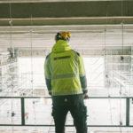 Foto av person med arbeidsklær og Betonmast-logo på ryggen som ser ut over en innendørs byggeplass