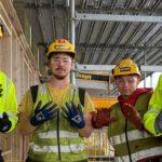 Fire menn i arbeidsklær på byggeplass