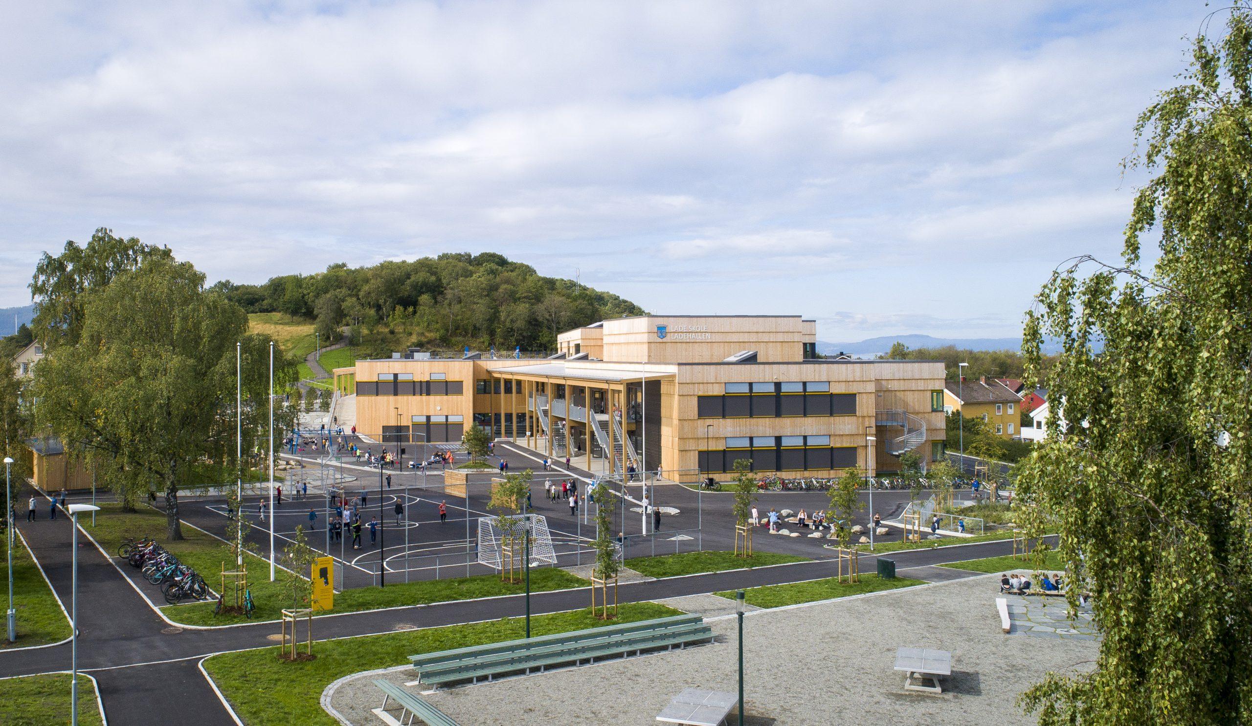 Foto av skolebygg i tre og skolegård