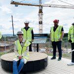 Foto av en kvinne og fire menn på en byggeplass