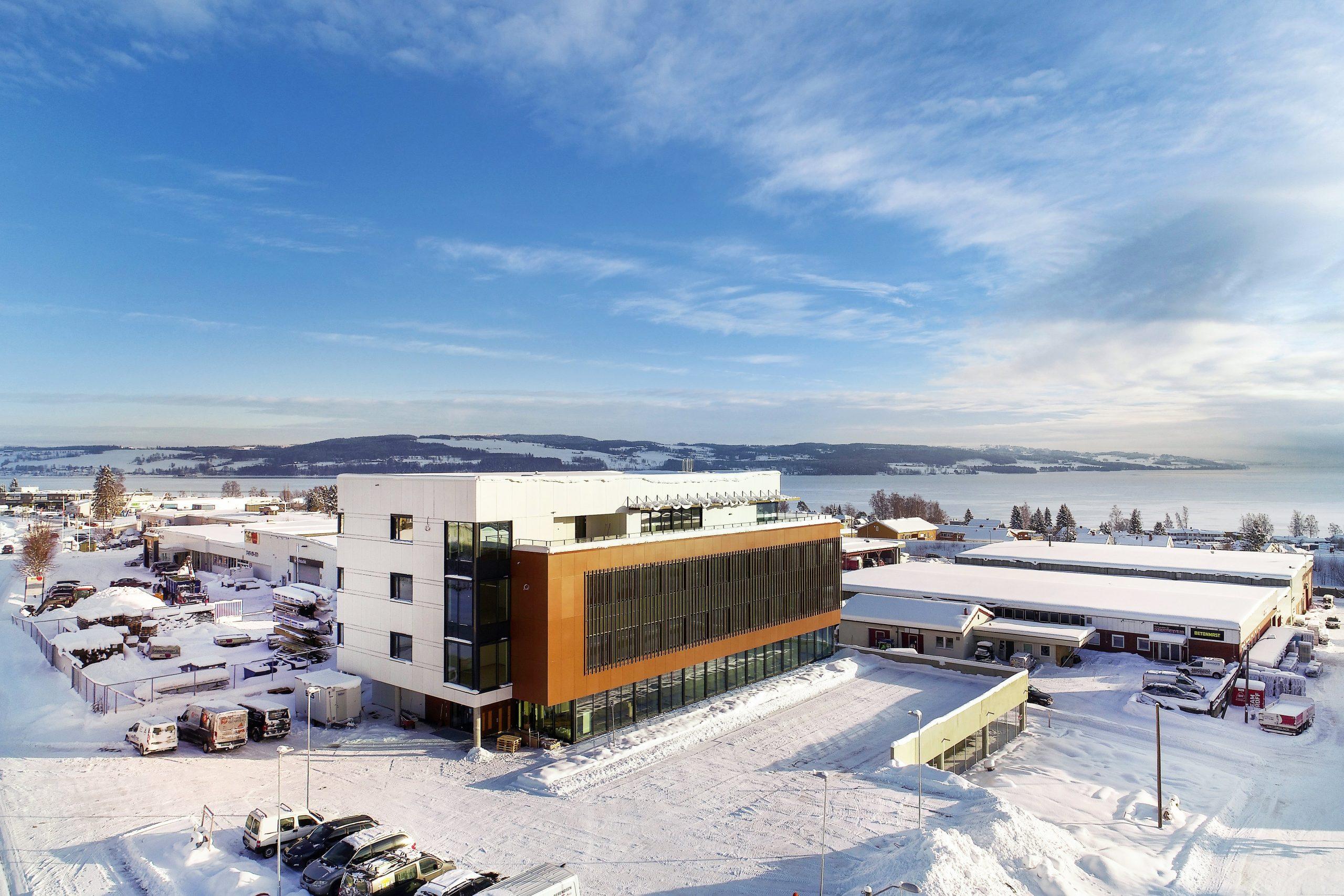 Foto av kontorbygg med en hvit del og en mørkere del, vinterlandskap med Mjøsa i bakgrunnen