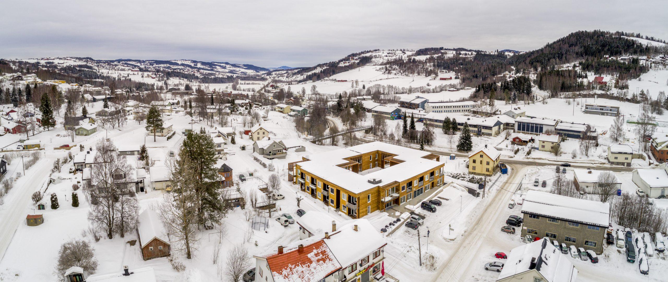 Dronefoto av et kvadratisk bygg med trefasade