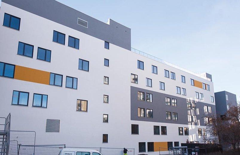 Foto av lyst bygg i seks etasjer, vinduer mm