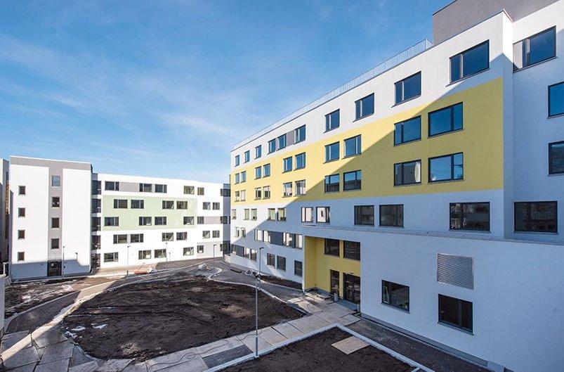 Foto av lyse bygg i seks etasjer, vinduer, bakgård mm