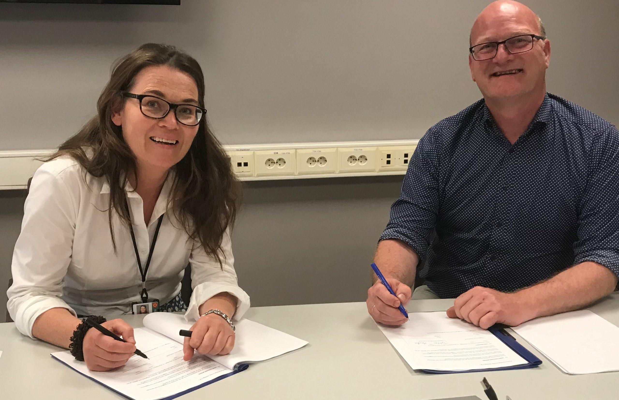 Foto av kvinne og mann ved signering av kontrakt