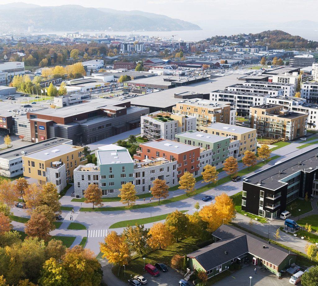 Illustrasjon av flere blokker med boligblokker, med Trondheimsfjorden og høst-trær i bakgrunnen